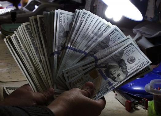 A money changer inspects U.S. dollar bills at a currency exchange in Manila
