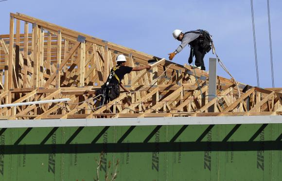 Workers install a roof on a multi-family building in Broomfield